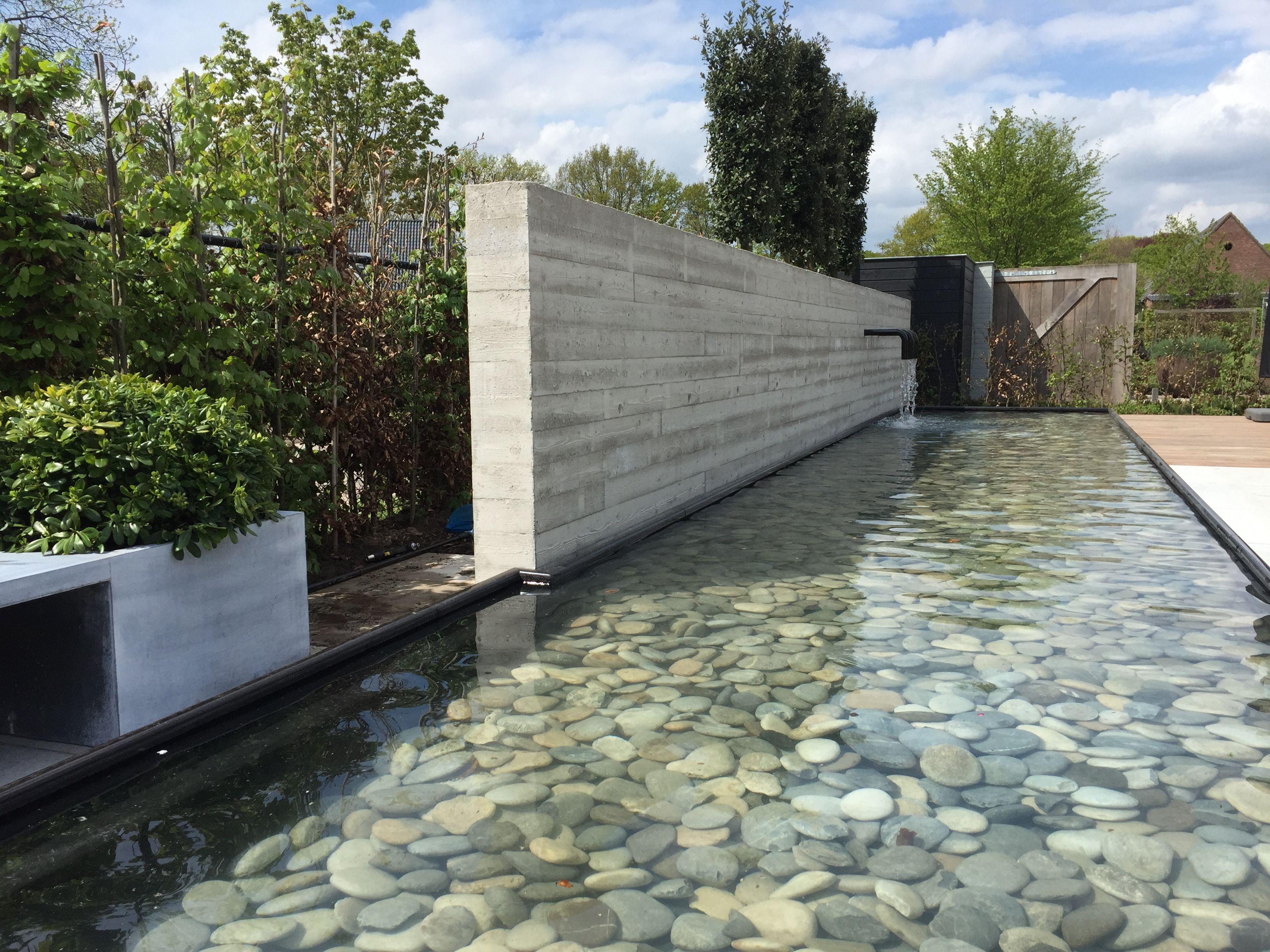 Spiegelvijver met betonnen muur waarin wateruitlopen zijn for Moderne waterpartijen tuin