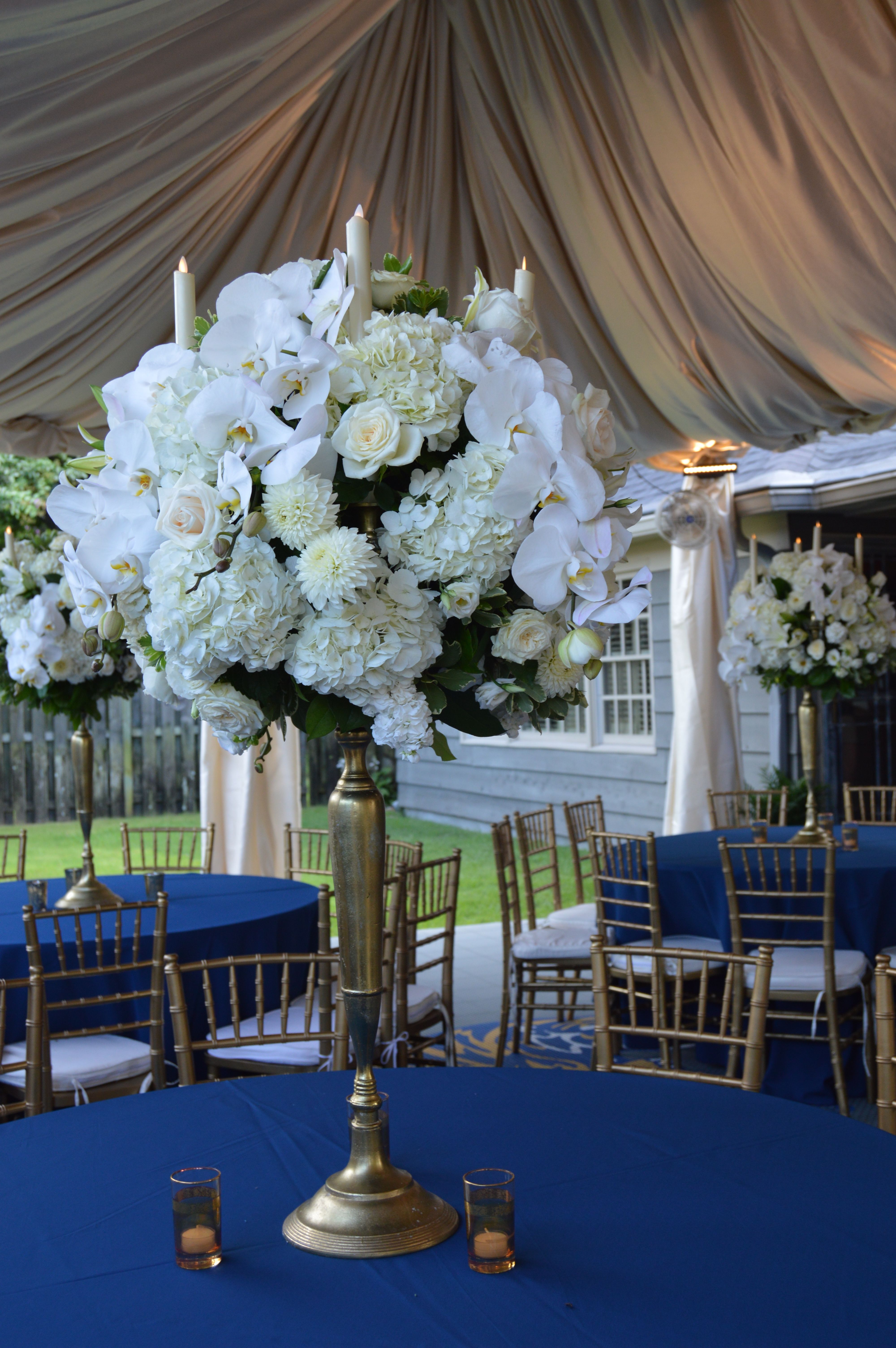Opulent golden candelabra arrangements with phalenopsis orchids, white roses, hydrangea, dahlias and taper candles.