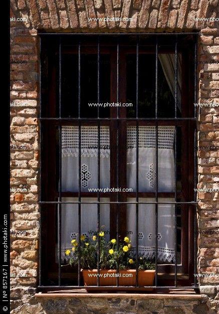 Imagen de http://p1.pkcdn.com/ventana-vieja-reja-y-flor-amarilla_857167.jpg.