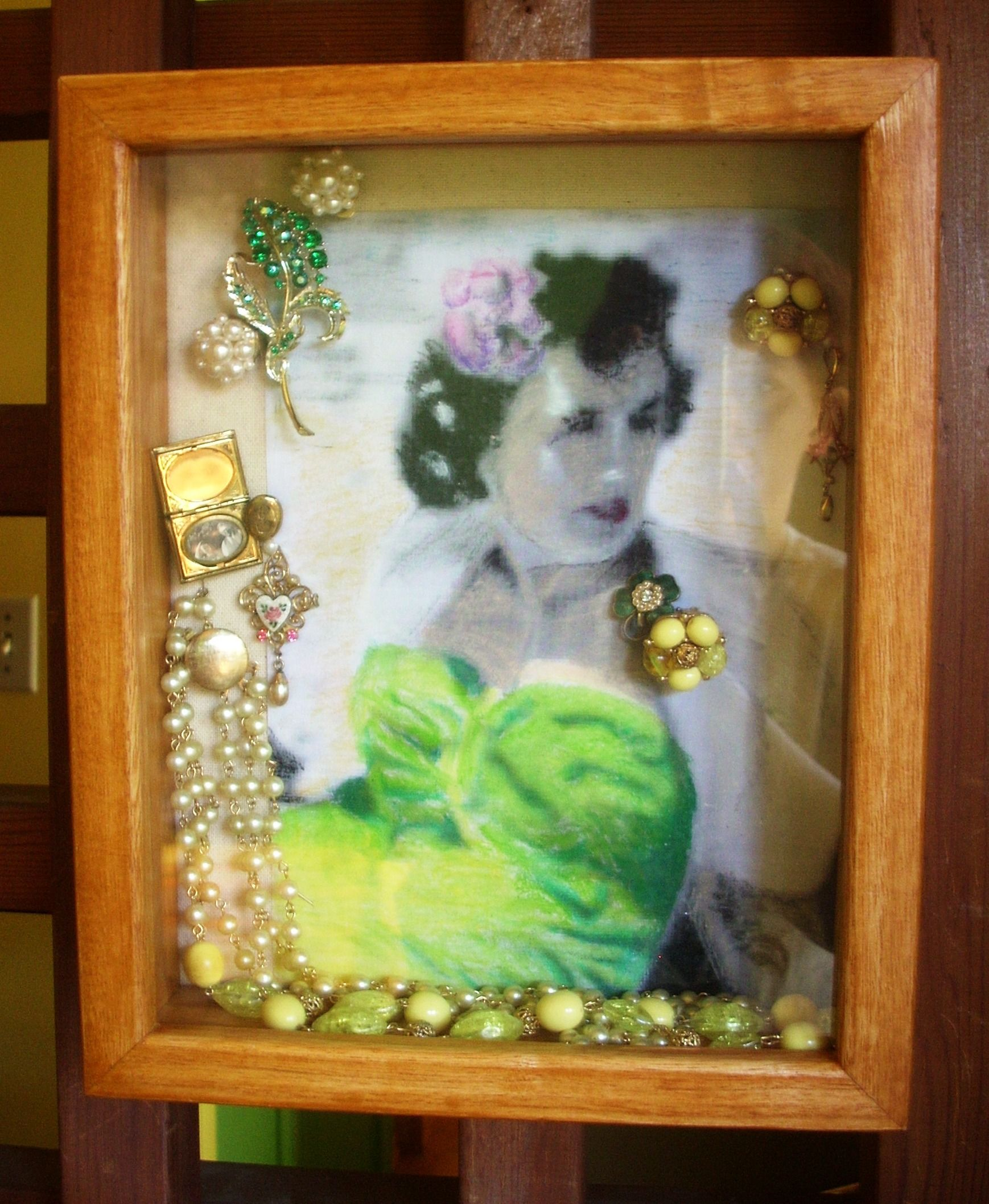 Shadowbox. Small picture of my mother from the 1940s, scanned, printed and hand-coloured with pastels. Added some of her jewelry.