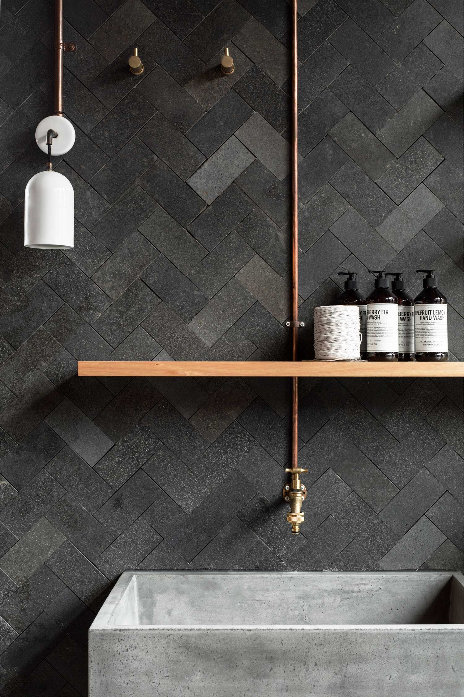 A blend of matte gray tiles set in a herringbone has such a soothing effect in this industrial bathroom.