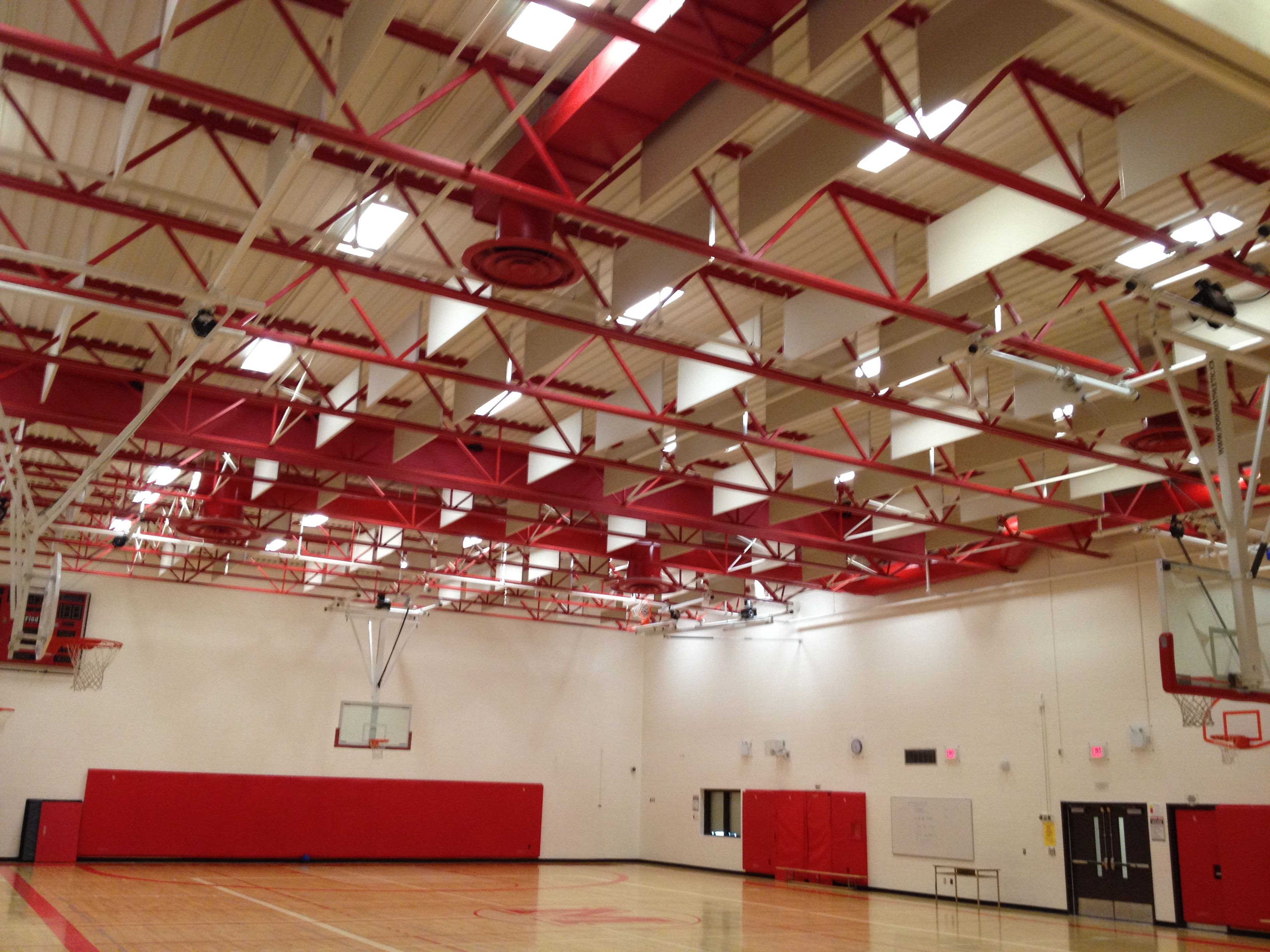 Suspended acoustic panels in a gymnasium ceiling