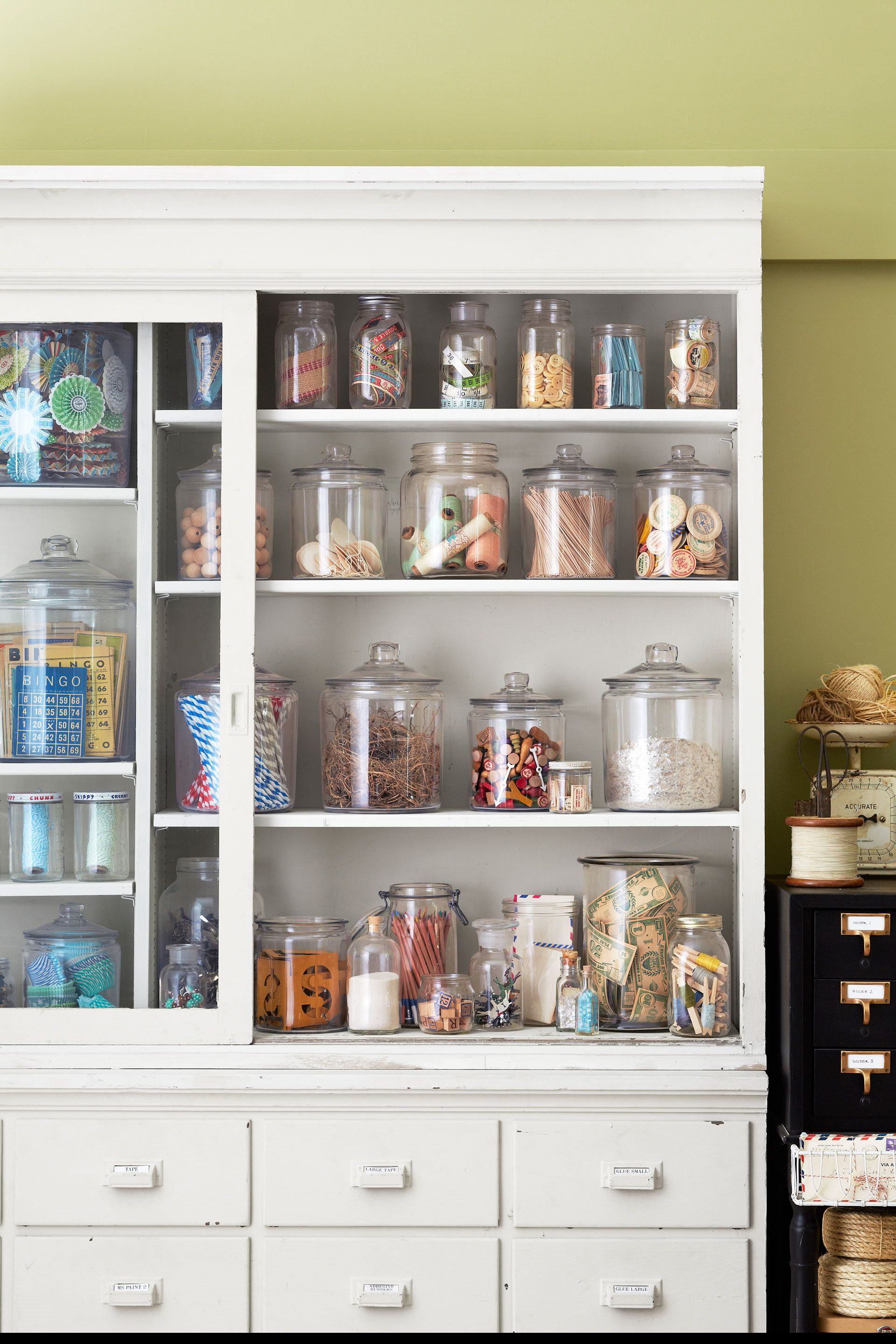 Crafting queen Cathe Holden uses an antique nine-foot-high apothecary cabinet to store her crafting supplies. But to curb chaos, Holden groups items together in an assortment of new and vintage glass jars. See more of Cathe's craft room makeover ideas. - CountryLiving.com