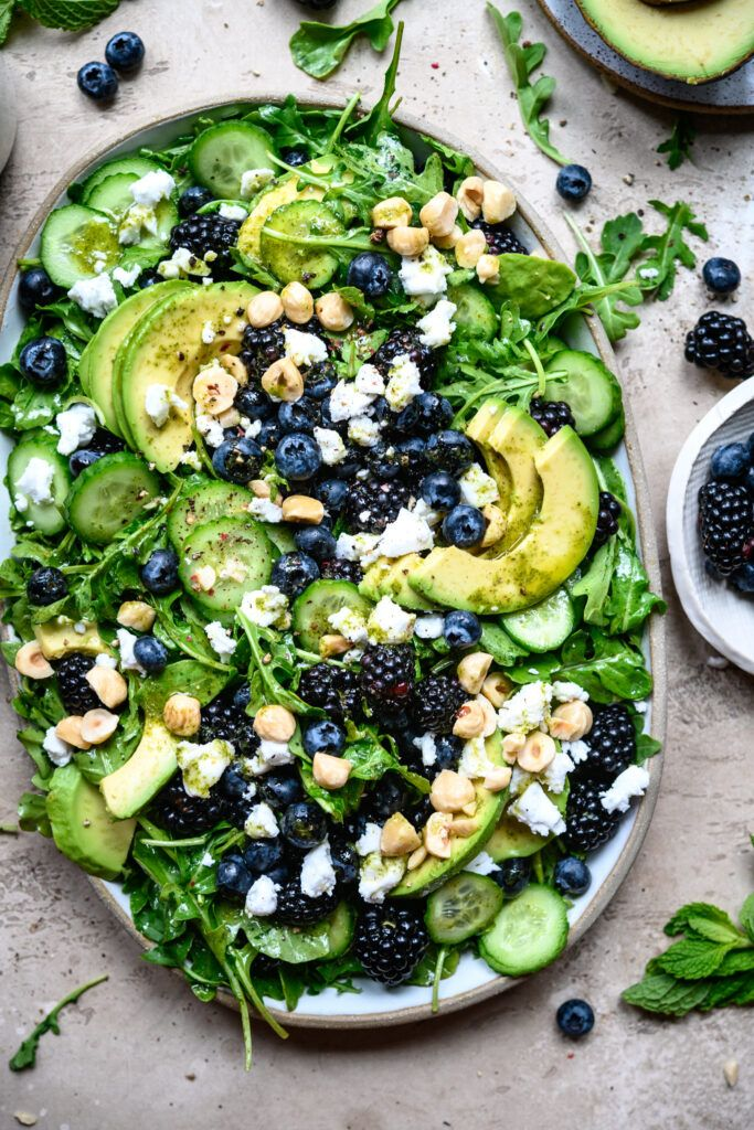 This summery salad makes the most of fresh produce with an arugula base, fresh blackberries, blueberries, cucumber, avocado, hazelnuts, vegan feta and a lime mint vinaigrette. #summersalad #blackberrysalad #arugulasalad #fruitsalad #berrysalad #blueberrysalad #veganfeta #veganrecipes #vegansalad #vegandinner #veganlunch #foodphotography   crowdedkitchen.com