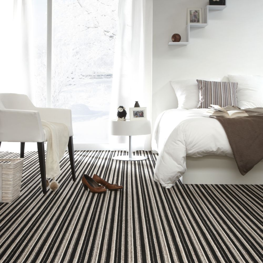 Modern bedroom with stylish bed and striped carpet