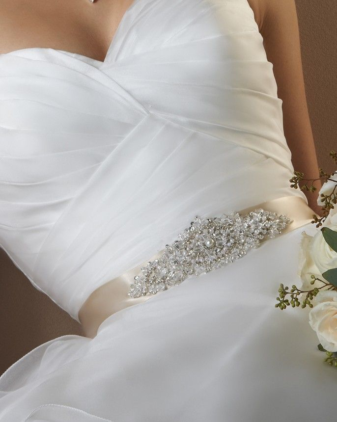 9310 A sparkling beaded and rhinestone motif is centered along the satin ribbon that ties in the back.