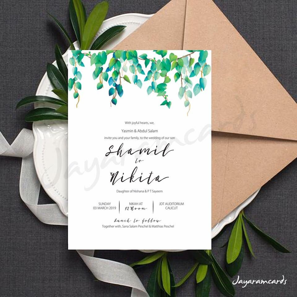 simple white invitation card with green leaf design and