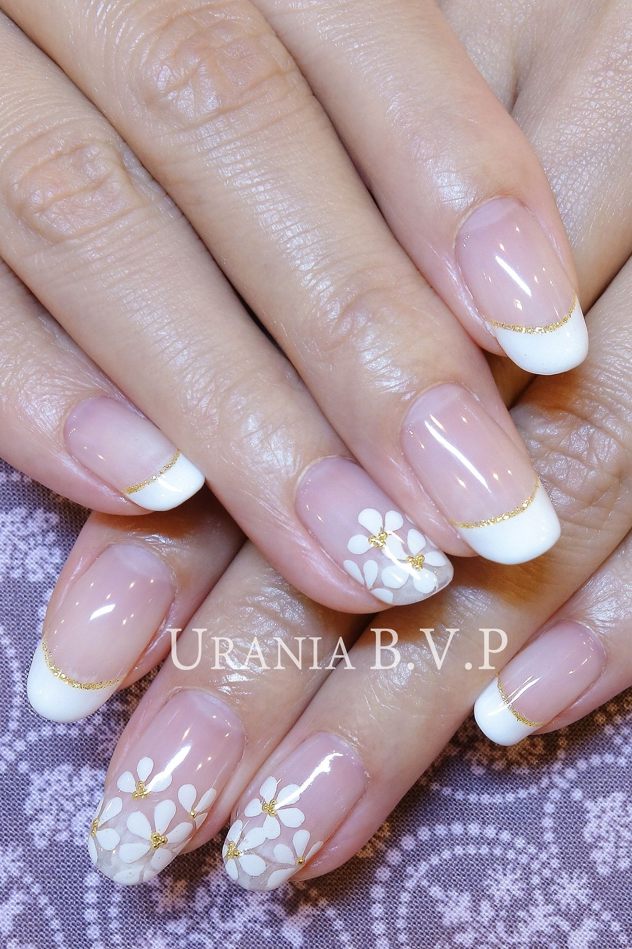 White flower nail art on a white french manicure with golden accents ...