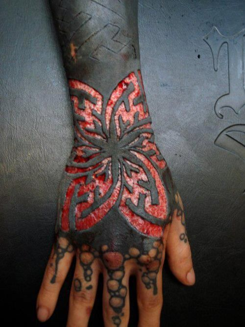 Scarification on a tattooed arm. The beauty here is taboo right now but I can appreciate the person's dedication to what they do. Incredible art.