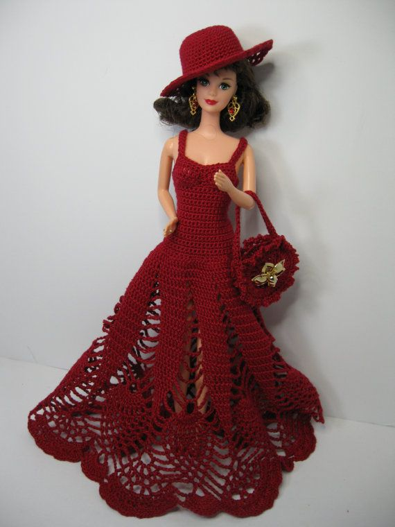 All inclusive gift! Just WOW! This is a Barbie collector type of dress and doll. Beautiful Barbie doll and fabulous handmade crochet dress, red floor length pineapple design. This item comes with the dress, black and red boa, crocheted hat, crocheted purse and shoes. The Barbie doll has eyelashes and beautiful earrings. The Barbie doll has 1966 marked on the back.    She comes with red shoes. The gold flower on the purse and hat are vintage clip-on earrings. They can be clipped on the hat or…
