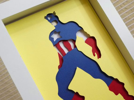 "Captain America Layered Paper Cut Art Piece 5""x7"" Shadowbox FrameThese Paper CutOuts are designed using Scale Vector Graphics and cut using a paper cutter for precision details. This piece has extra layers that"