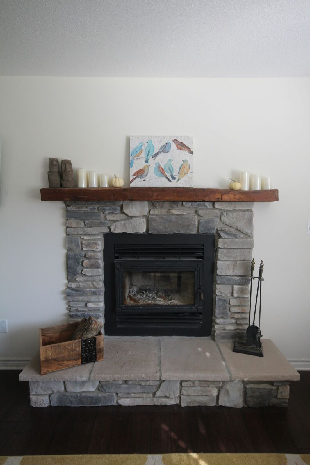 stone fireplace surround with rustic mantle and raised hearth