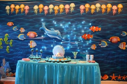 Under The Sea Party ~ Giant ocean backdrop with twinkle lights on the wall behind the backdrop to make it look like the sun filtering through the water... what an AWESOME idea!
