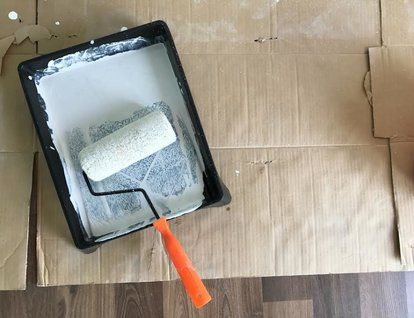 cardboard on flooring with a paint roller and tray on top on top new diy garage storage and organization ideas minimal budget garage make over id=66018