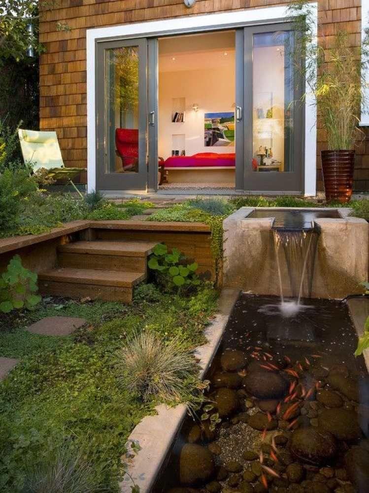 Cascade de jardin avec bassin plein de poissons rouges