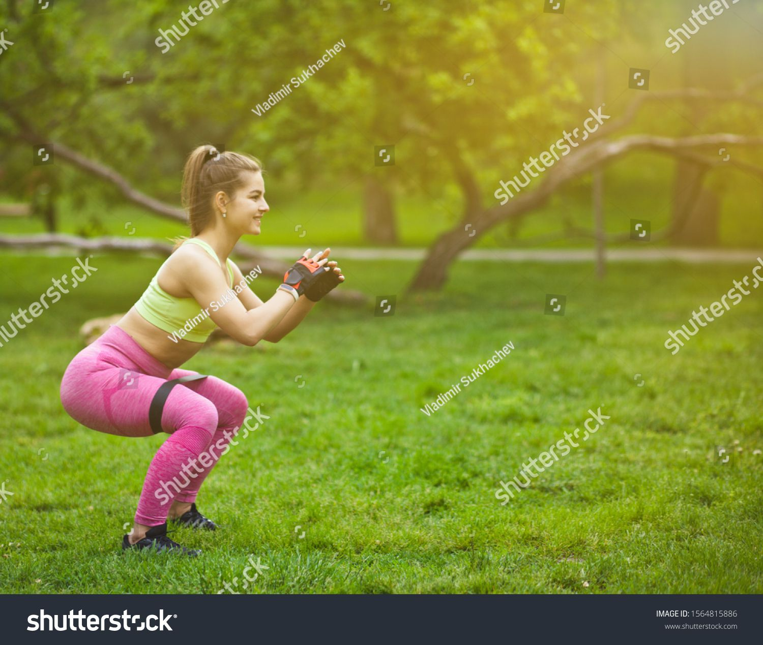 Sporty woman doing squats with fitness gum expander in the park outdoors #Sponsored , #Ad, #squats#f...
