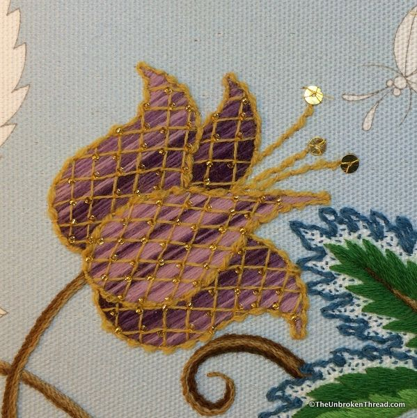 Once the shading was finished, there were two decorative stitches to do before adding the beads. The first was the trellis. In this case I laid the trellis one section at a time. The next step was couching down a double 5 5 of 5 thread around each section of the fritillary. Lastly, I added the tiny gold beads at the cross points of the trellis and the gold spangles.