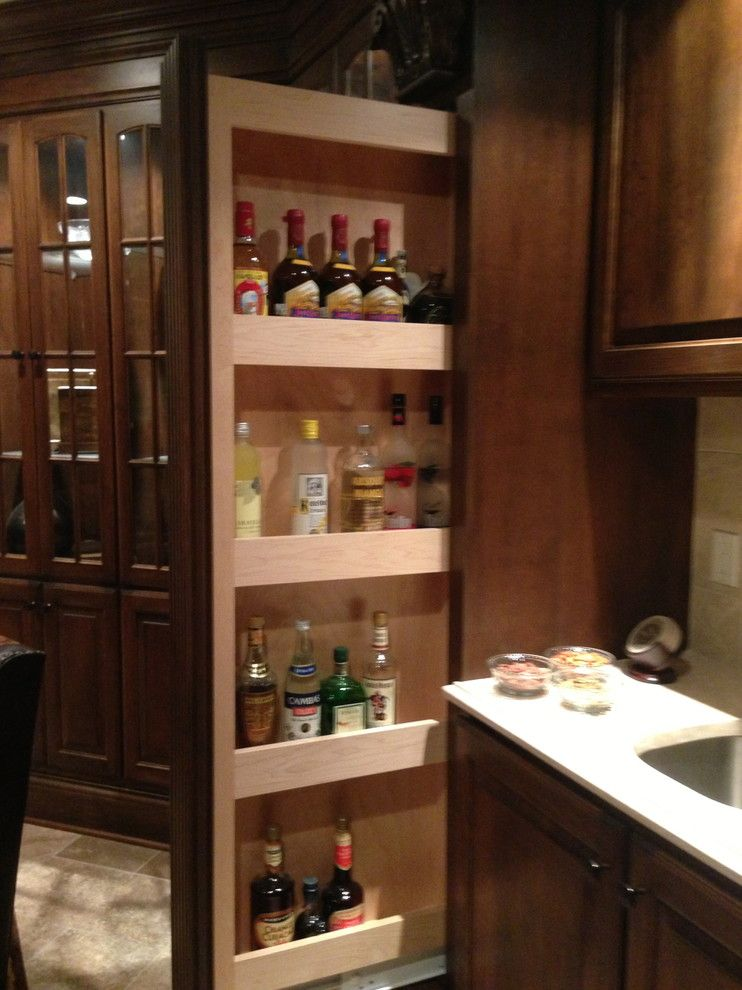 Hidden liquor cabinet basement traditional with cherry for Built in drinks cabinet