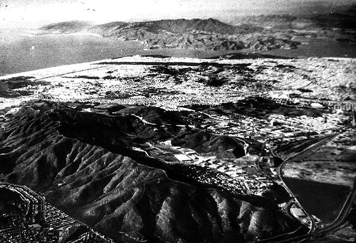 San Bruno Mountain in the foreground, looking north-northwest with the Golden Gate visible at the northern edge of San Francisco & Marin County across the water. Highway 101 runs across the lower right hand corner, enclosing the remains of Brisbane Lagoon to its left (west). Pacific Ocean in upper left corner. San Bruno Mountain is the last island of wildness at the southern edge of San Francisco & its peninsula.The first view of it is north on Highway 101 from the airport toward San…