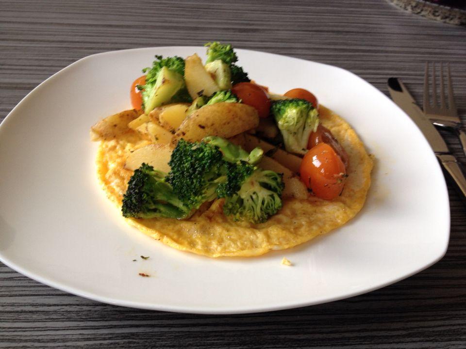 Omelet met gebakken aardappelen en groente.