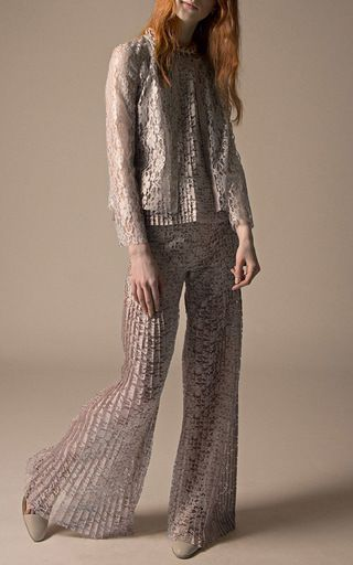 Rendered in sheer floral lace, this **Huishan Zhang** pant feature a high rise with a flat front design, knife pleats falling from the leg, and a flared silhouette.