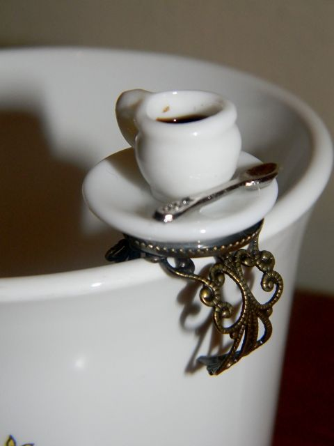 Tea time is any time with this fun Tea Cup fashion ring. Ceramic cup and saucer are set atop an antique bronze tone filigree fashion band. Pressure adjustable, one size fits most adults.
