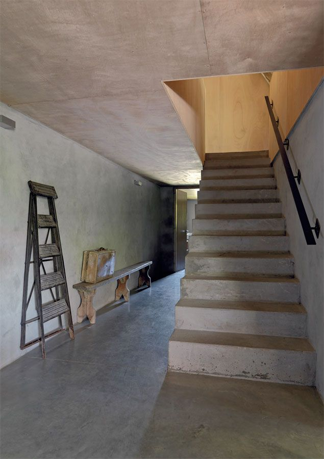 Una escalera de cemento alisado se eleva con sus líneas geométricas - paredes de cemento