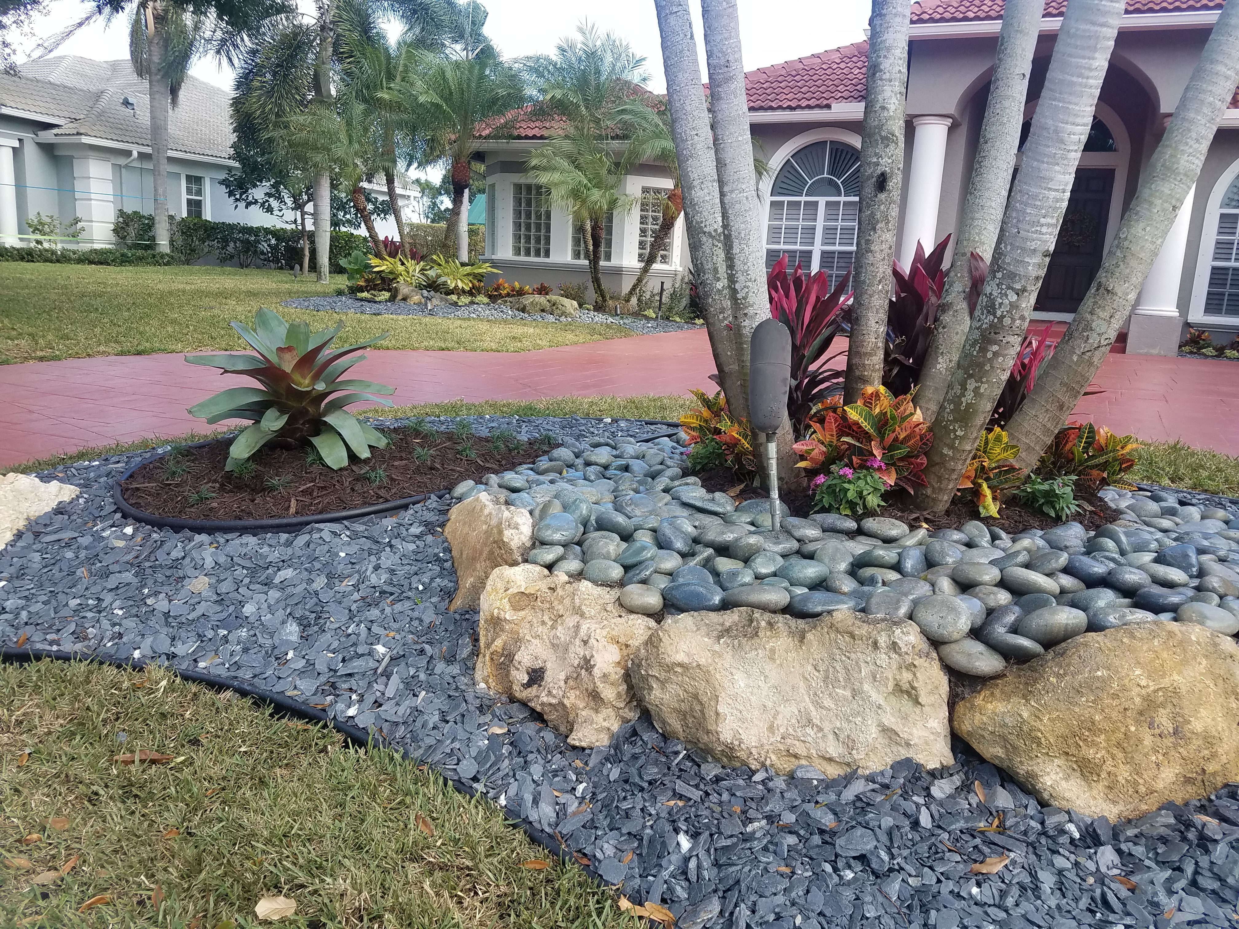 Landscape For Driveway Center Island With Tropical Plantings Cap Rock Boulders Mexican Beach Pebble Black Slate Stone Trim
