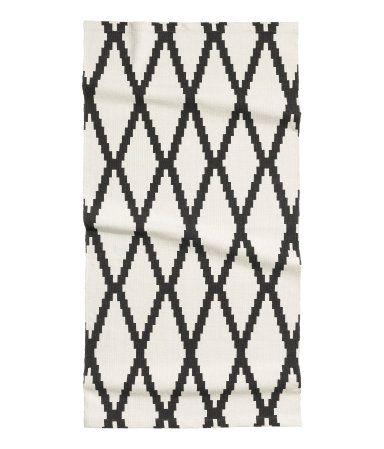 Rechteckiger Webteppich aus Baumwolle mit Musterdruck auf der Oberseite.