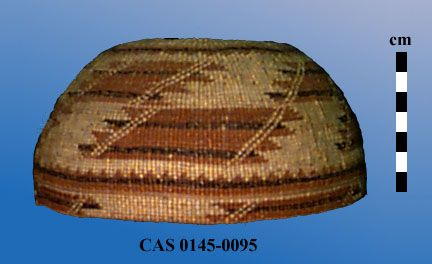"""Hemispherical woman's hat with flat base and curved sides; Woven primarily in plain twining with 3-strand twining on base and near rim; Design is in bear grass and woodwardia and maidenhair fern and is divided into 3 registers; Whirling sunburst motif is on crown; Middle and rim registers show stacked parallelograms with serrated ends (""""Sharp Tooth"""" pattern). Dimensions (cm)Height = 9.0, Max Diam = 19.0"""