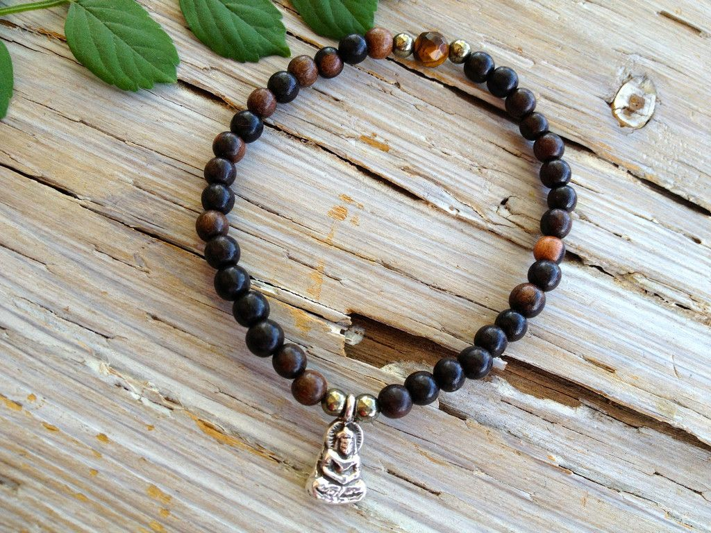 """BUDDHA'S WISDOM BRACELET  """"The only real failure in life is not to be true to the best one knows."""" -Buddha This tiger ebony wood, pyrite and tiger eye bracelet is a gentle year-round reminder to live in an om-azing life.  Buddha charm is made of sterling silver.  Stretch bracelet measures 7"""", sized to fit most wrists."""