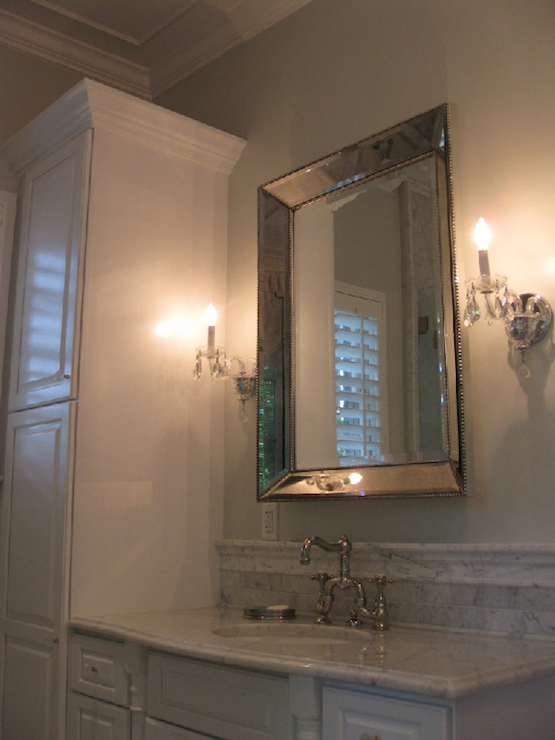 Glam bathroom with soft gray walls, crystal sconces flanking ...