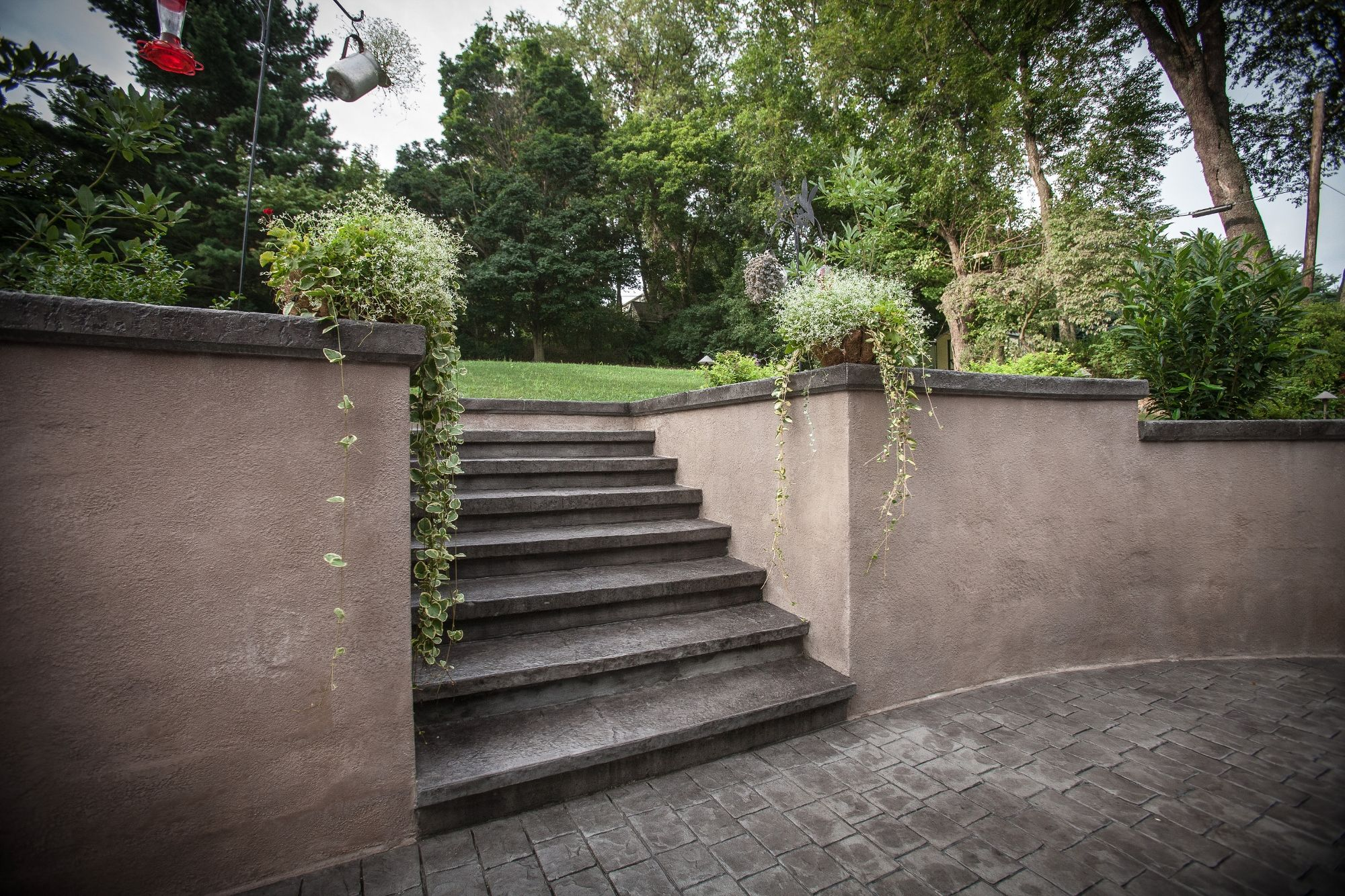 Gray Stamped Concrete Patio With Beige Concrete Retaining Wall Concrete Retaining Walls Landscaping Retaining Walls Backyard Retaining Walls