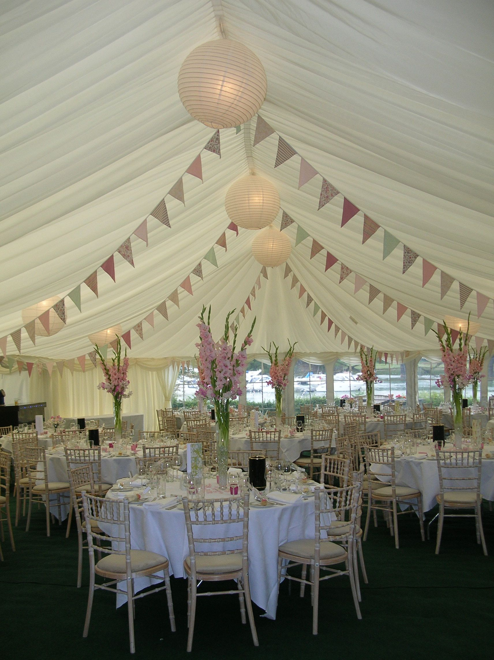 Pastel bunting and tall pink flowers make a beautiful for Indoor marquee decoration