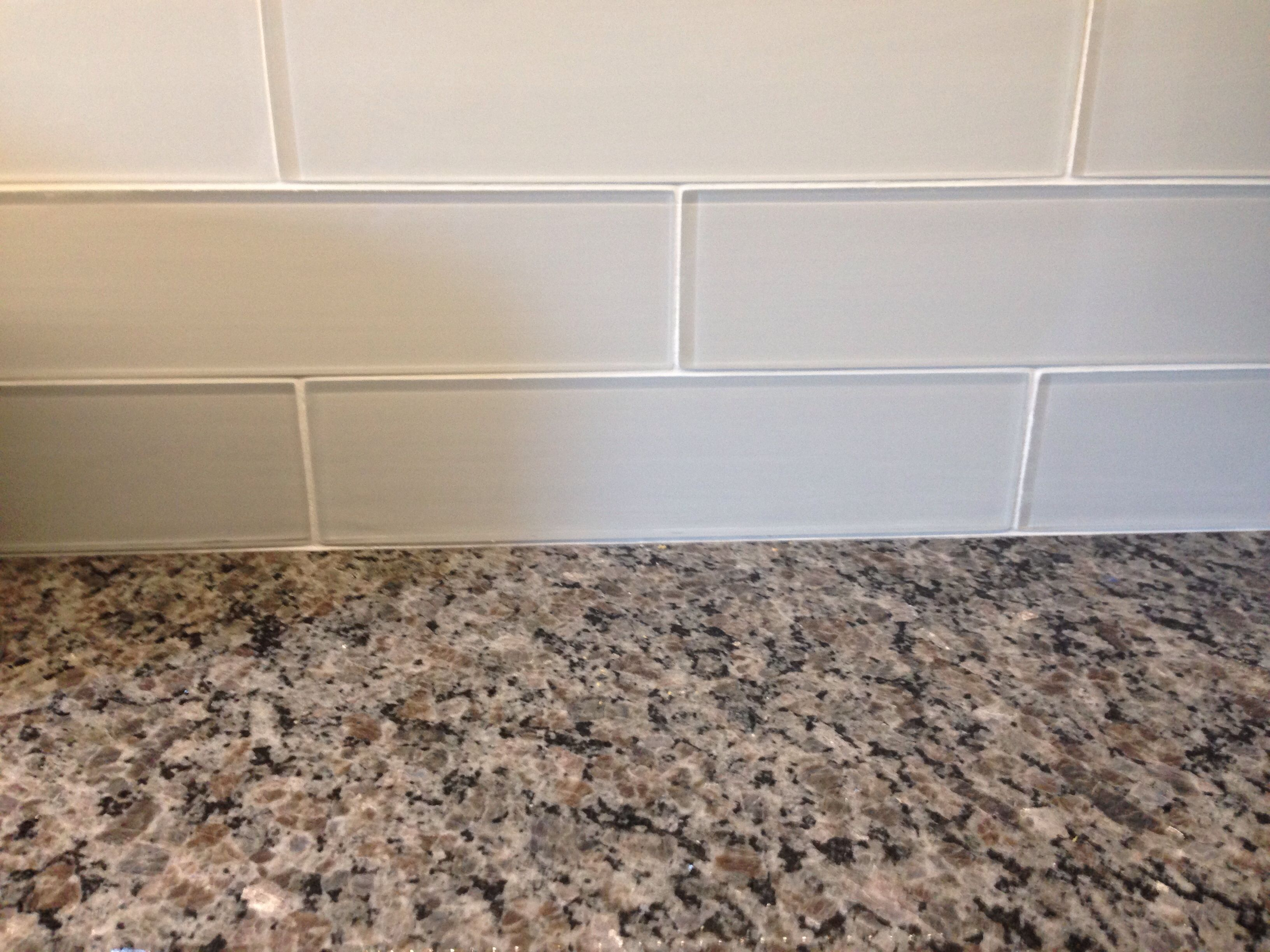 New Caledonia Granite Countertops And White Glass Tile Backsplash