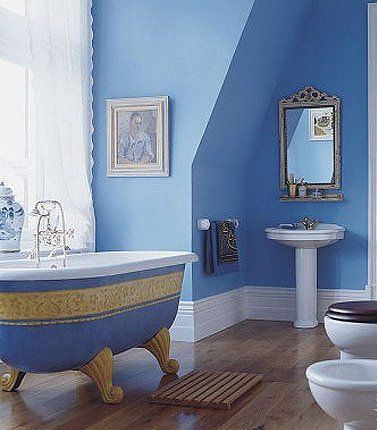 show design of a bathtub. Claw foot stand alone tub  hardwood floor calm blue painted walls and natural light
