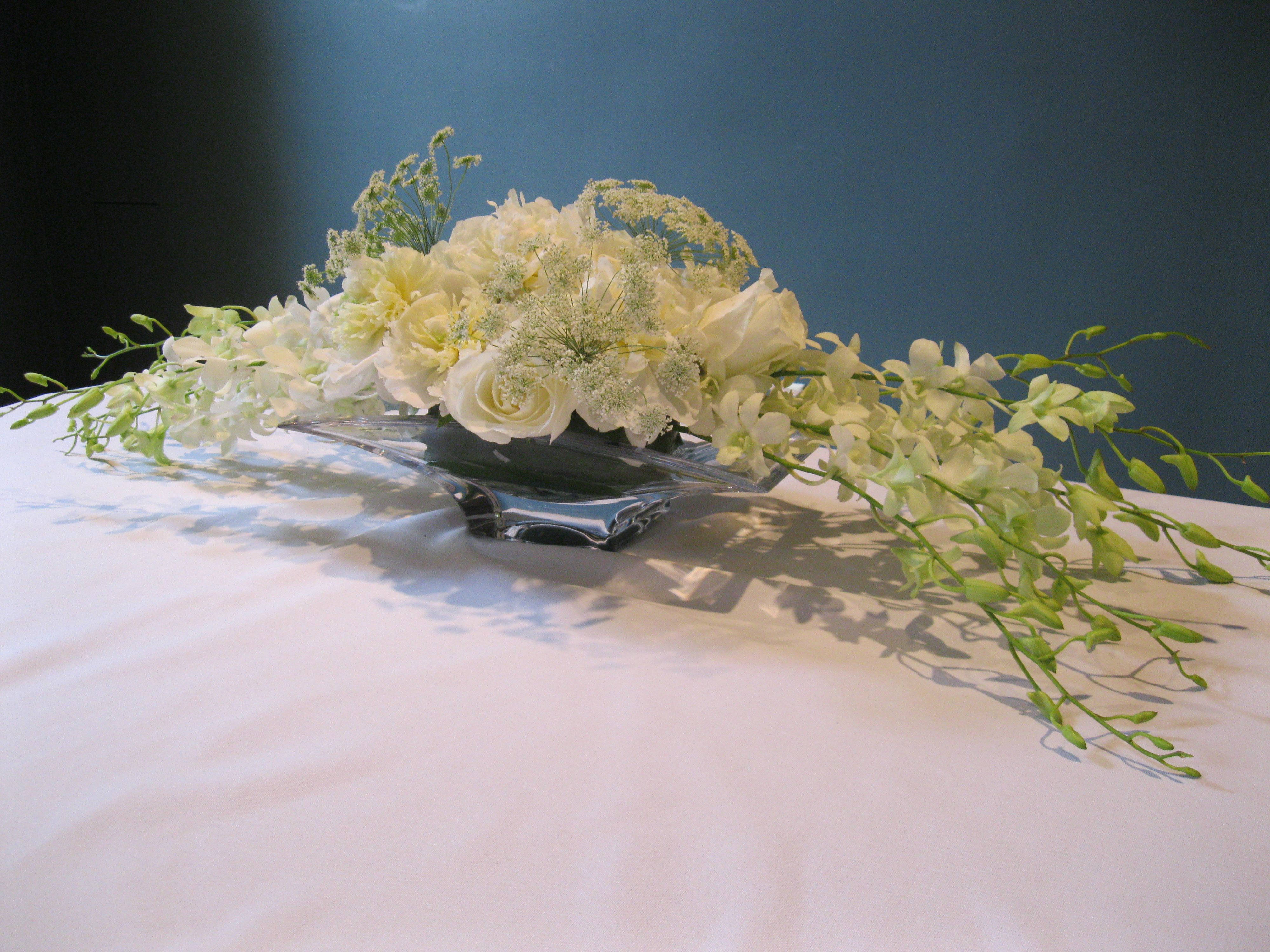 A sophisticated long and low white table centerpiece with
