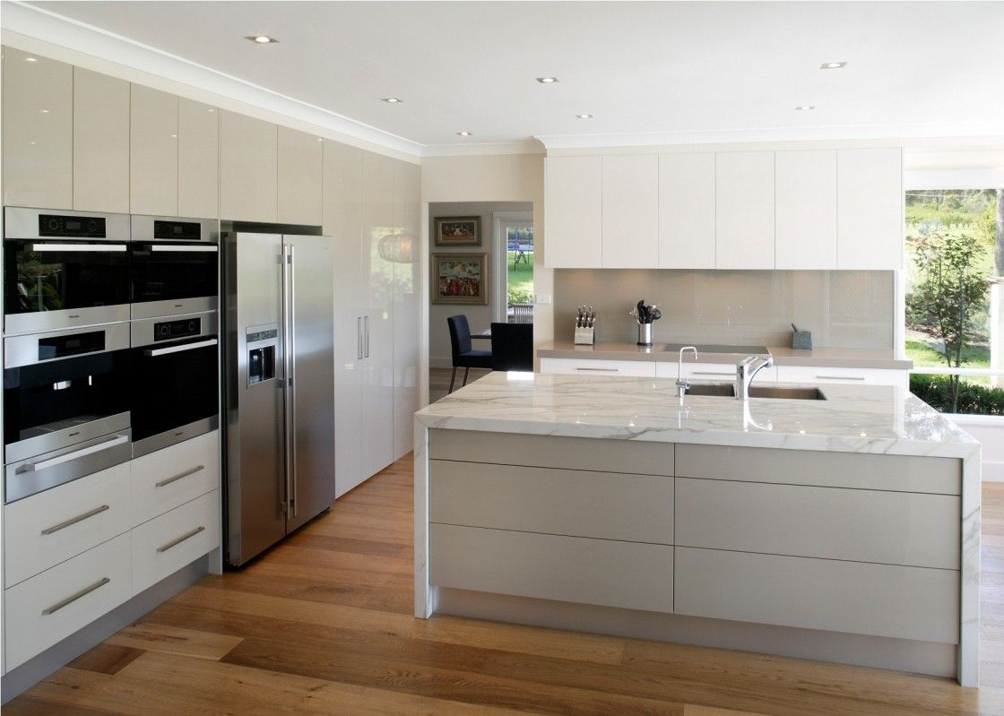 Fascinating Kitchen Design Picture Features Modern Large White Marble Island Top And High Gloss Cabinets Also Laminated Wooden Floor