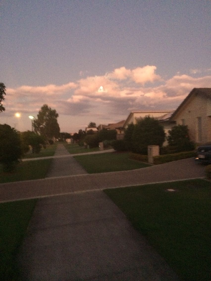 Moon behind the clouds at dusk