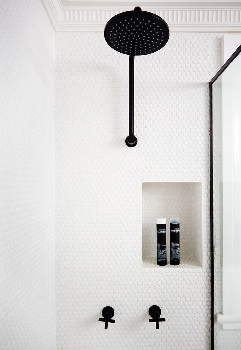 bathroom with white penny shower tile black fittings
