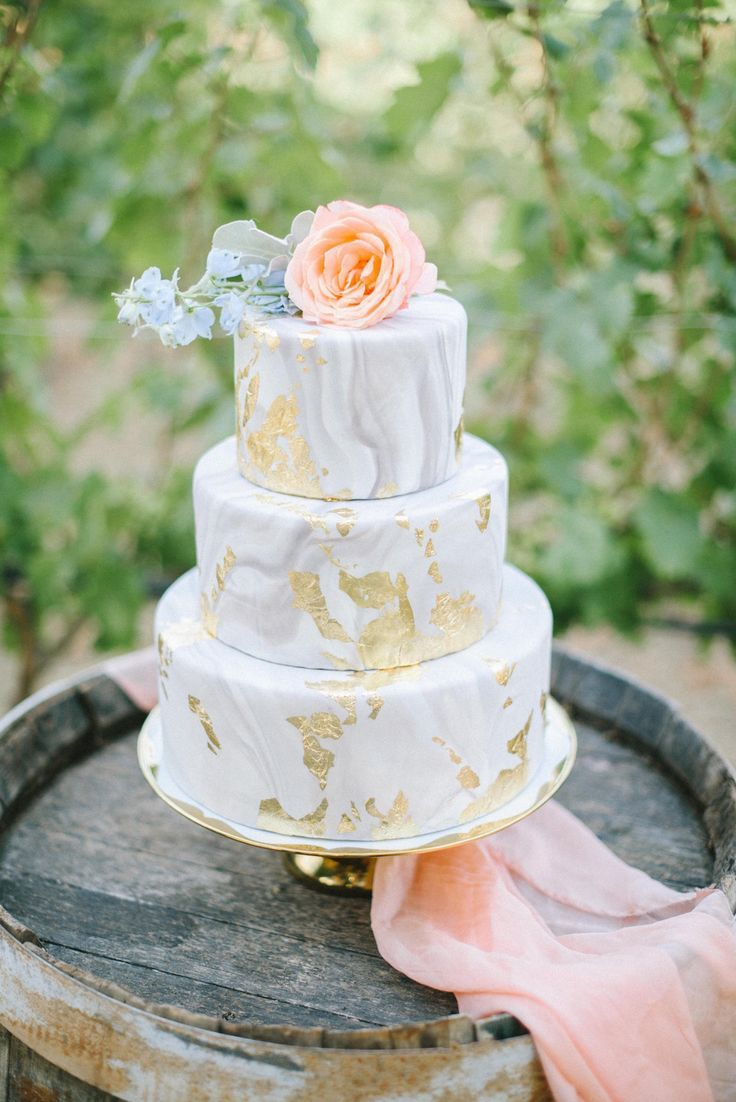 A beautiful gray and gold marbled wedding cake with peach accents ...