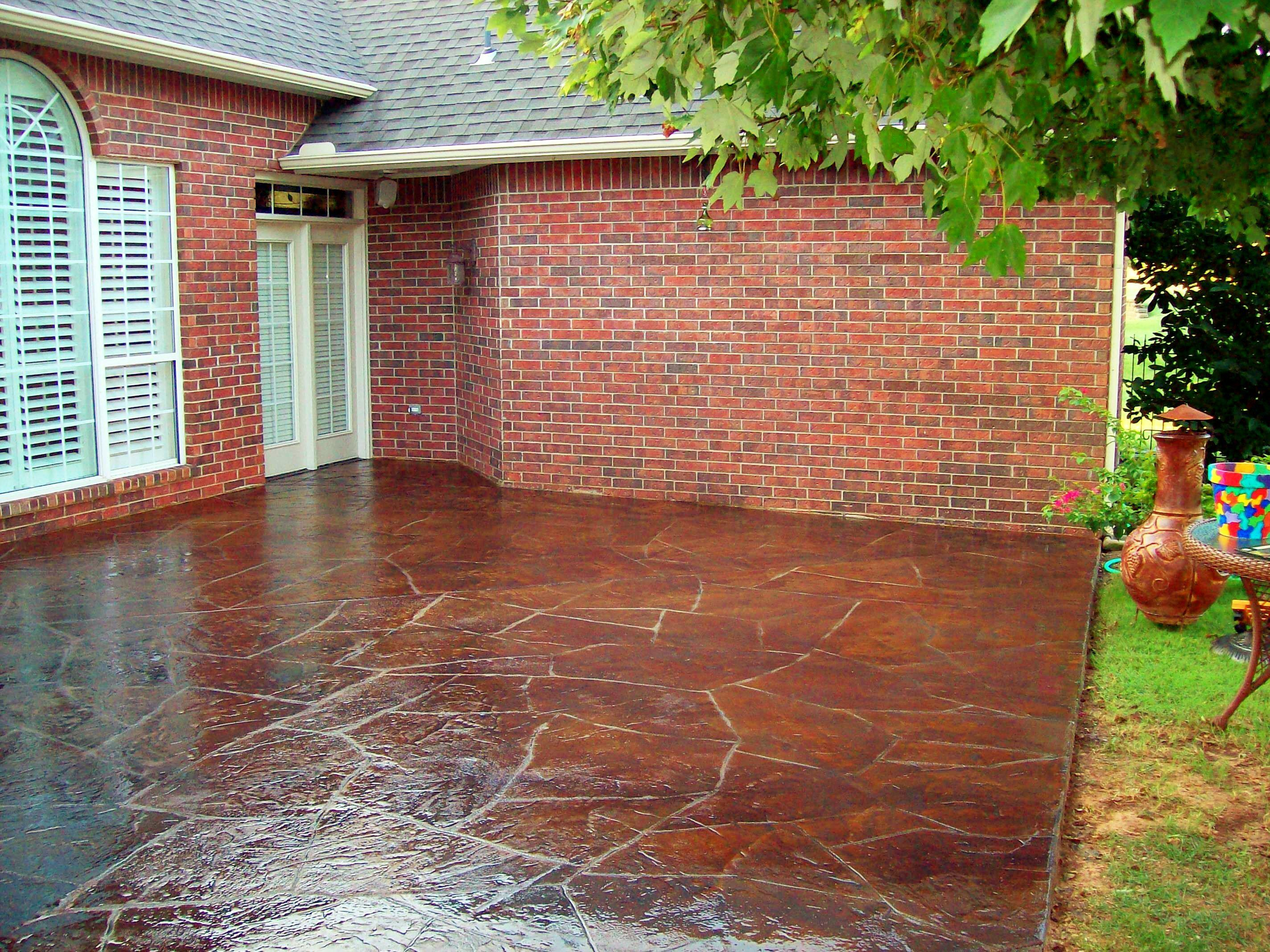 Brown stone stained concrete patio floor with red brick for Red brick patio ideas