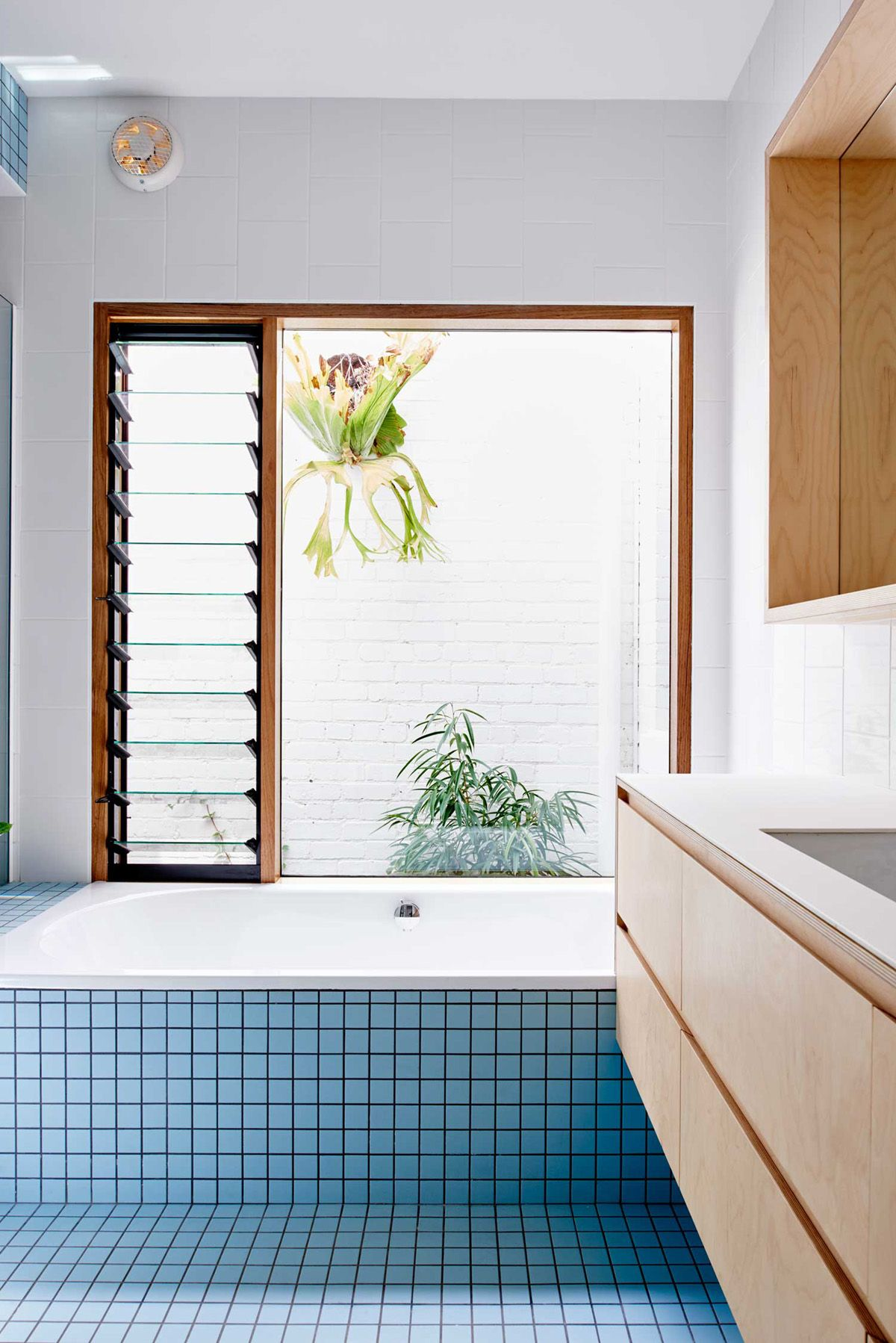 baby blue square tiles and light wood in this modern bath renovation ...