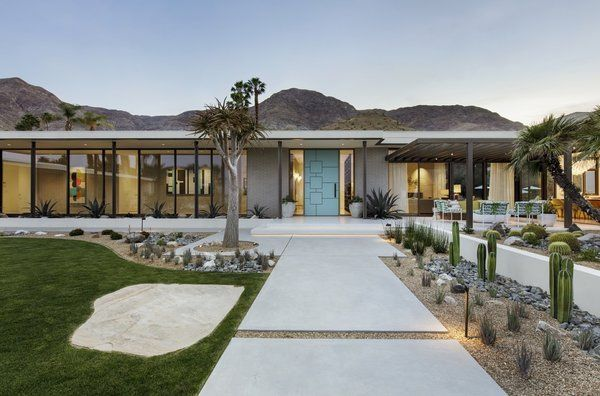 Exterior, Flat RoofLine, Brick Siding Material, House Building Type, and Glass Siding Material Poured concrete walkways flanked by desert landscaping lead to the architect-designed front door painted bright blue. #walkwaystofrontdoor