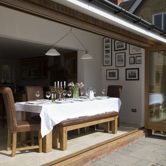 Modern Conservatory Dining Area With Bi Folding Doors And Brown Leather Chairs