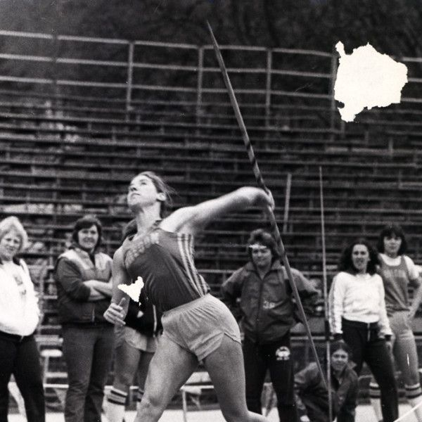 Black and white photo of University of Oregon javelin thrower Sally Harmon about to release a throw at Hayward Field in 1981. That same year Harmon became the first Duck to become an individual champion in the Association for Intercollegiate Athletics for Women with a throw of 177-10 at the AIAW championships in May. ©University of Oregon Libraries - Special Collections and University Archives