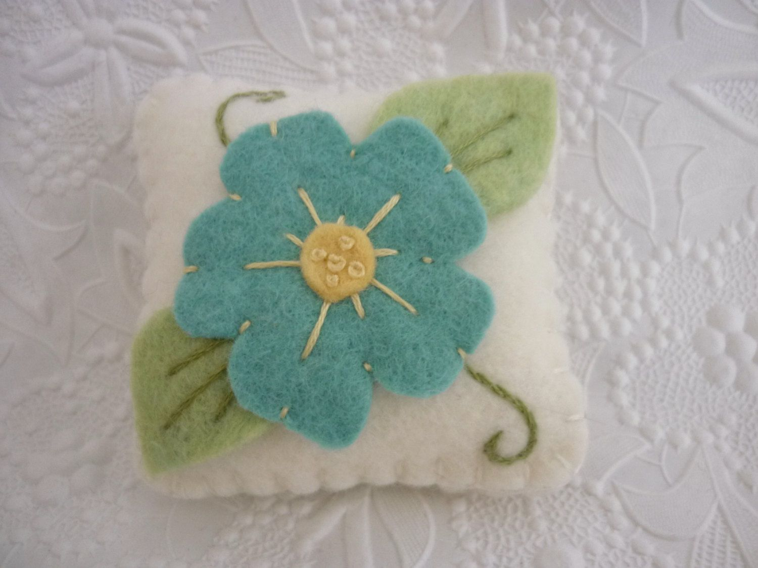 Primitive Flower Pincushion Felt Wool Penny Rug Style Applique  This little pincushion is made from top quality felted wool. The flower is beautiful deep aqua blue color, with a pastel yellow center with tiny French knots in the middle. Mint green wool felt was used for the leaves with hand stitched veins in the center.  All pieces are hand stitched to the pincushion.  Measures 2 1/2 wide, 2 1/2 tall and is firmly stuffed with poly fill.  Would make a great gift for any quilter.  If...