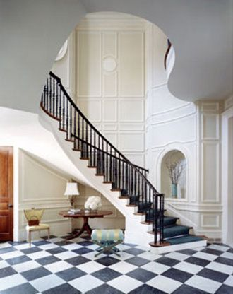 Grand entryway with sweeping staircase and classic black & white ...