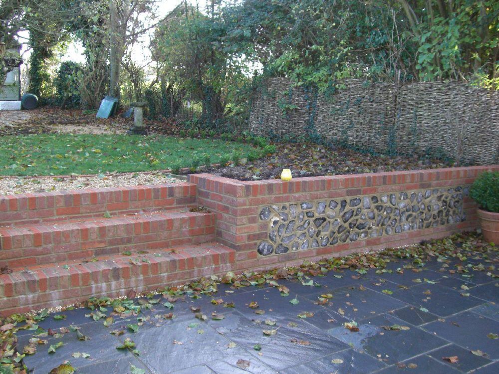 Slate patio with brick and flint retaining wall. | Brick ...