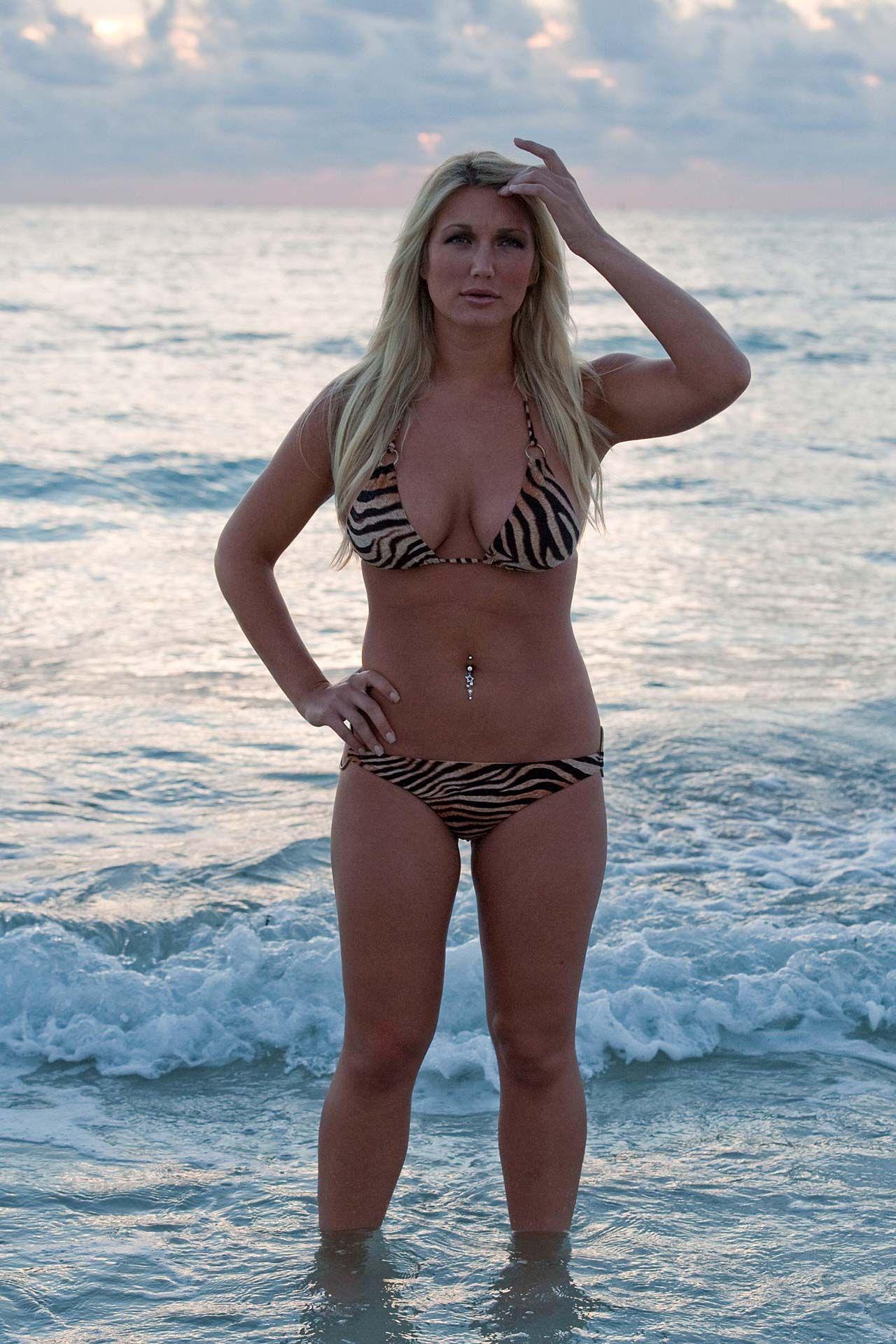 Avec une silhouette atlétique et les cheveux blonde sans soutien-gorge (taille 34D) en bikini sur la plage